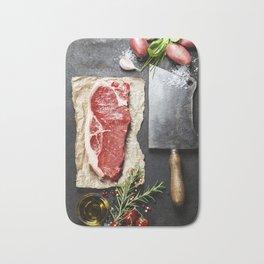 vintage cleaver and raw beef steak on dark background Bath Mat