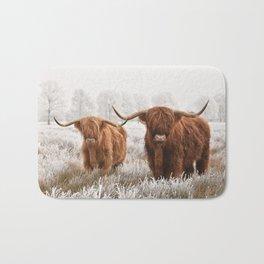 Hairy Scottish highlanders in a natural winter landscape. Bath Mat