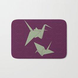 Origami paper cranes on purple waves Bath Mat