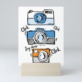 Cartoon cameras with colors hand Say cheese Mini Art Print