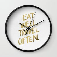 eat Wall Clocks featuring Eat Well Travel Often on Gold by Cat Coquillette
