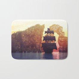 A pirate ship off an island at a sunset Bath Mat