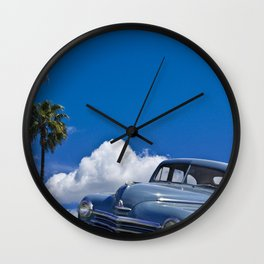 Vintage Blue Plymouth Automobile against Palm Trees and Cloudy Blue Sky Wall Clock