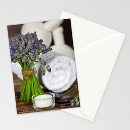 Fresh  lavender flowers, zen stones,Herbal massage balls , candle and towel over wooden surface Stationery Cards