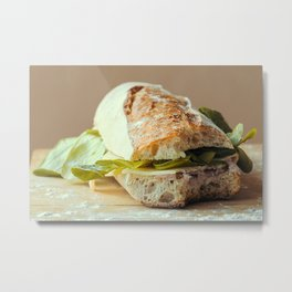 Baguette cut in two, bitten, stuffed with cheese, salad, baked ham Metal Print