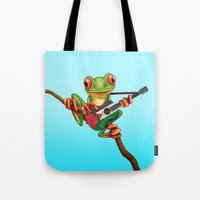palestine Tote Bags featuring Tree Frog Playing Acoustic Guitar with Flag of Palestine by Jeff Bartels