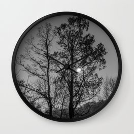 Hiding sun behind black and white trees Wall Clock