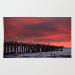Surfers riding waves off Seal Beach pier at sunset Rug