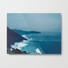 Under A Misty Grey Sky The Blue Waves Meets The Jagged Cliff On The Sore Metal Print