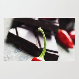 Dark chocolate with chili pepper over wooden background Rug