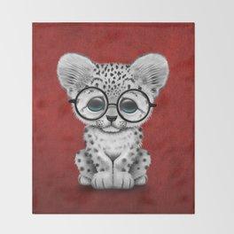 Cute Snow Leopard Cub Wearing Glasses on Deep Red Throw Blanket
