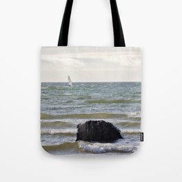 Windsurfer and black stone at gray sea Tote Bag