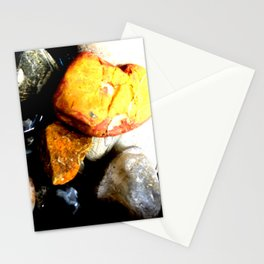 Bright orange rock resting on top of other stones - abstract geological nature Stationery Cards