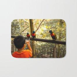 Feeding parrots at a birdpark Bath Mat