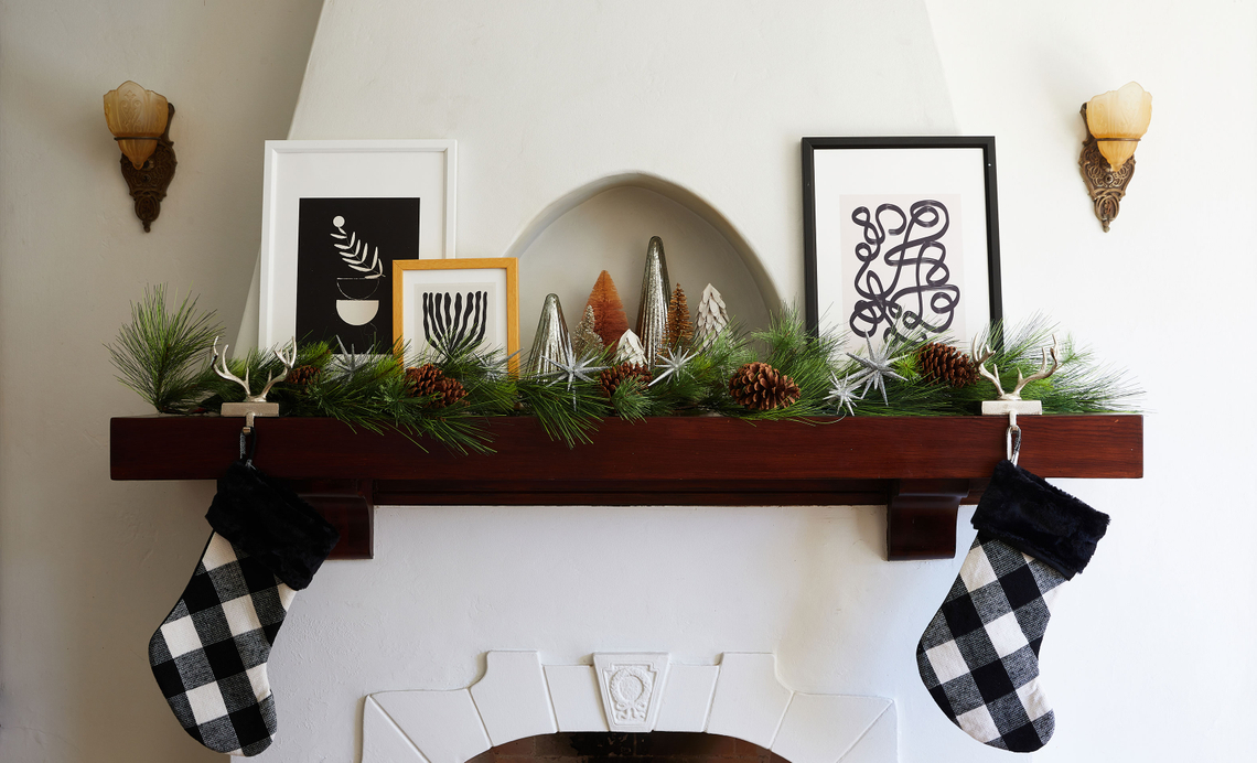 festive framed prints on a mantel with wreaths and small decorative christmas trees