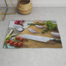 Knife with healthy food - vegetables, onion, salad, tomatoes, potato placed on a cutting board with Rug