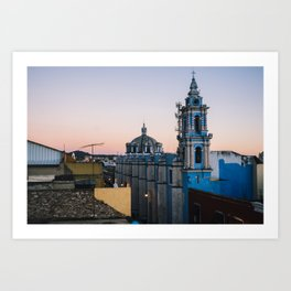 A blue colonial church taken from a rooftop at sunset Art Print