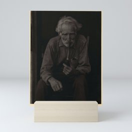 Doris Ulmann  (1882–1934), Elderly, bearded man in polka-dot shirt, seated in chair, smoking pipe Mini Art Print