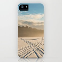 Crossing tracks on snow covered frozen lake iPhone Case