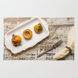 Three fruit tarts presented on an elegant antique china plate Rug