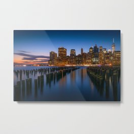 Sea side New York city in the evening with enlighten tall buildings, calm water and blue sky Metal Print