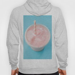 Top view of a strawberry smoothie in a plastic cup with a straw on a blue background. Hoody