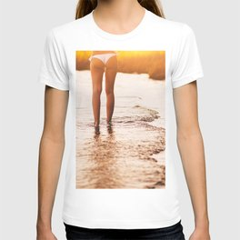 Low Section Of Young Woman in a white bikini walking Toward Sea on Beach at the sunset. Concept Summ T-shirt