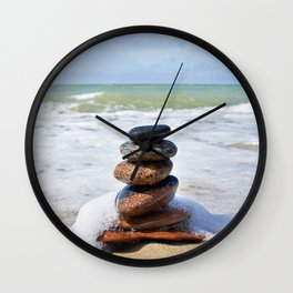 Stones in pyramid and wave on sand beach Wall Clock