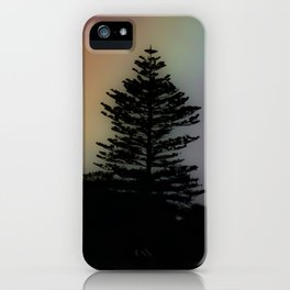 Purple hued rainbow sky behind silhouetted conifer trees iPhone Case