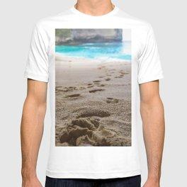 Footprint on a white sand beach with blue ocean waves T-shirt