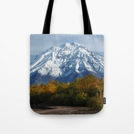 Autumn panoramic view of snow-capped rocky mountain, yellow-orange forest at foot of volcano on Kamc Tote Bag
