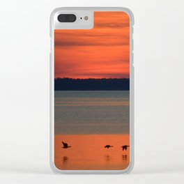 A flock of geese flying north across the calm evening waters of the bay Clear iPhone Case