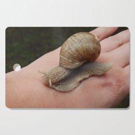 Snail crawling the green grass in garden Cutting Board