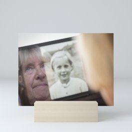 Senior woman looking an image of herself as a child on a tablet computer Mini Art Print