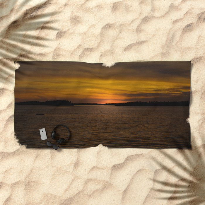 The sun goes down and night falls Beach Towel