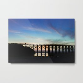 Couple watching the sunset while childeren play in the water underneath them Metal Print