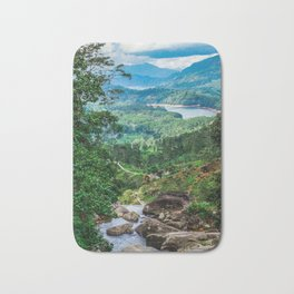 Green valley overview with mountains and waterfall Bath Mat