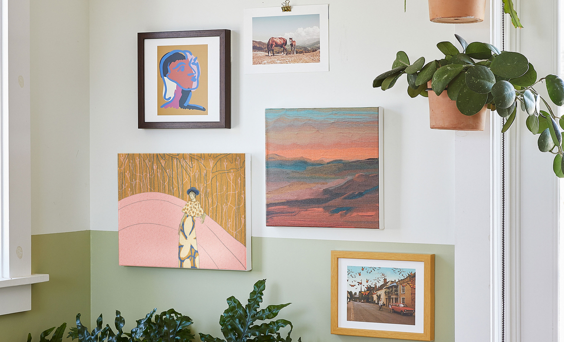 gallery wall of painterly framed & canvas prints on a sage and cream colored wall