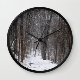 Snow falling on hiking path in woods Wall Clock