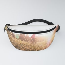 Woman walking through meadow at sunset Fanny Pack