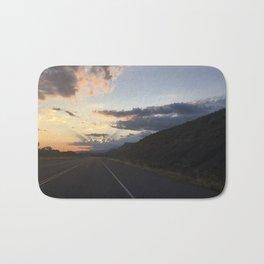 Sunlit clouds over an American road Bath Mat