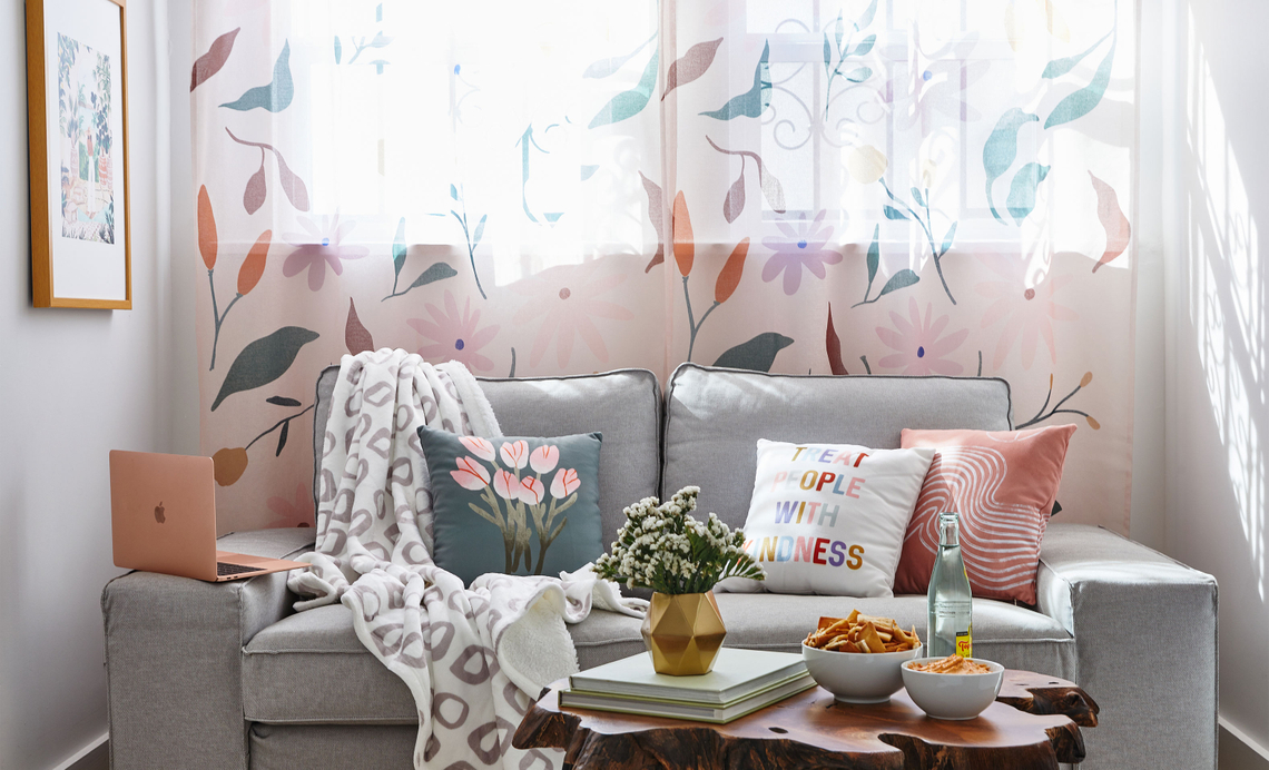 gray sofa with pillows and blankets under floral sheer curtains