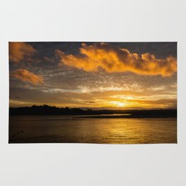 Sunset at the beach. Huge golden clouds by sunlight. Rug