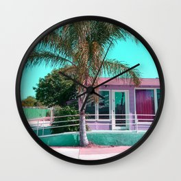 pink building in the city with palm tree and blue sky Wall Clock