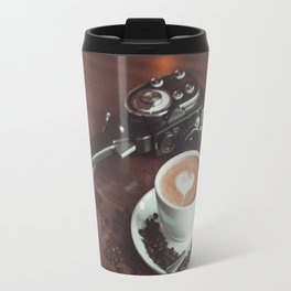 A cup of hot cappuccino placed on a table next to the old camera with lens and coffee beans Travel Mug