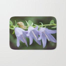 Eli the Snail and the Purple Flowers by Althéa Photo Bath Mat