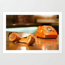 Handset of an orange telephone with dial placed on a wooden table inside a bar. Art Print
