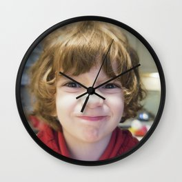 Child smiling and joking in a living room Wall Clock