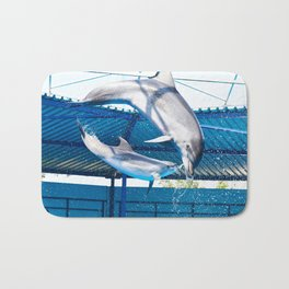 Dolphins jumping out of water on show Bath Mat