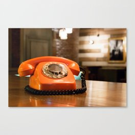A vintage plastic orange telephone with dial placed on a wooden table inside a bar. Canvas Print